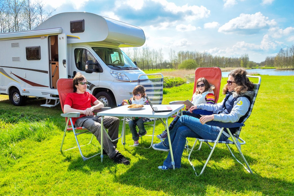 happy parents with children on holiday trip in motorhome