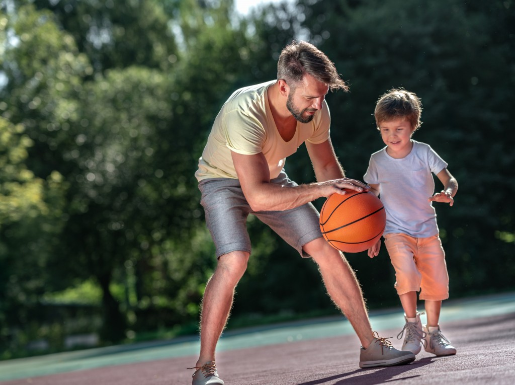 father playing basketball with his son